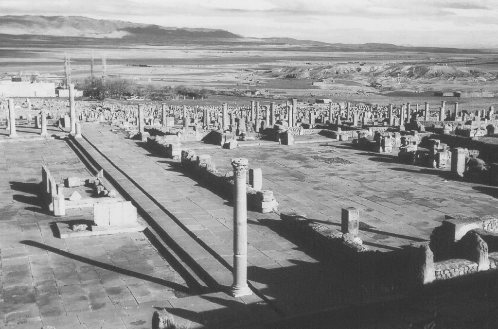 A landscape image depicting the ruins of Timgad, an ancient Roman city. The ruins are surrounded by severly eroded lands, which according to Lowdermilk are now only able to support a few hundred inhabitants living in the huts shown in the background.