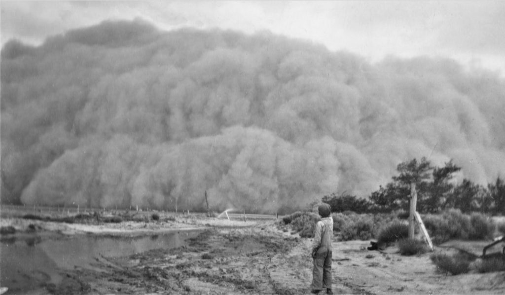 A black and white photograph depicting a young boy standing next to a stream pointing towards an oncoming, ominous-looking dust storm on the horizon. The boy is wearing overalls, a light colored long sleeved shirt, and a dark hat.