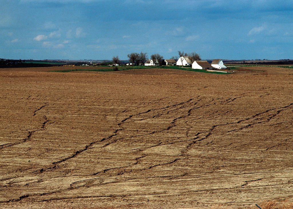 A landscape photograph of a field in Cass County, Iowa depicting a bare field with light brown soil with extensive sheet and rill erosion. A farmstead with white buildings is on the horizon, with blue skies and a few white clouds above.