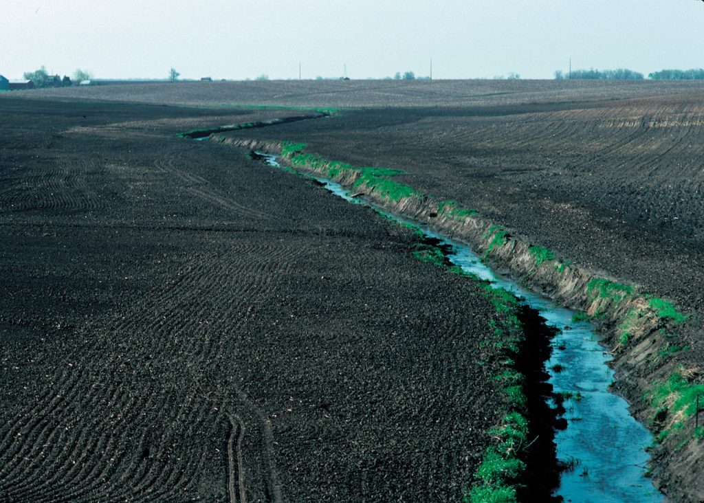A landscape photograph of a field with bare, black soil that was freshly tilled up to the edge of a stream that disects the landscape through the center of the image. The stream has sparse green plants, but is mostly bare due to recent streambank erosion.