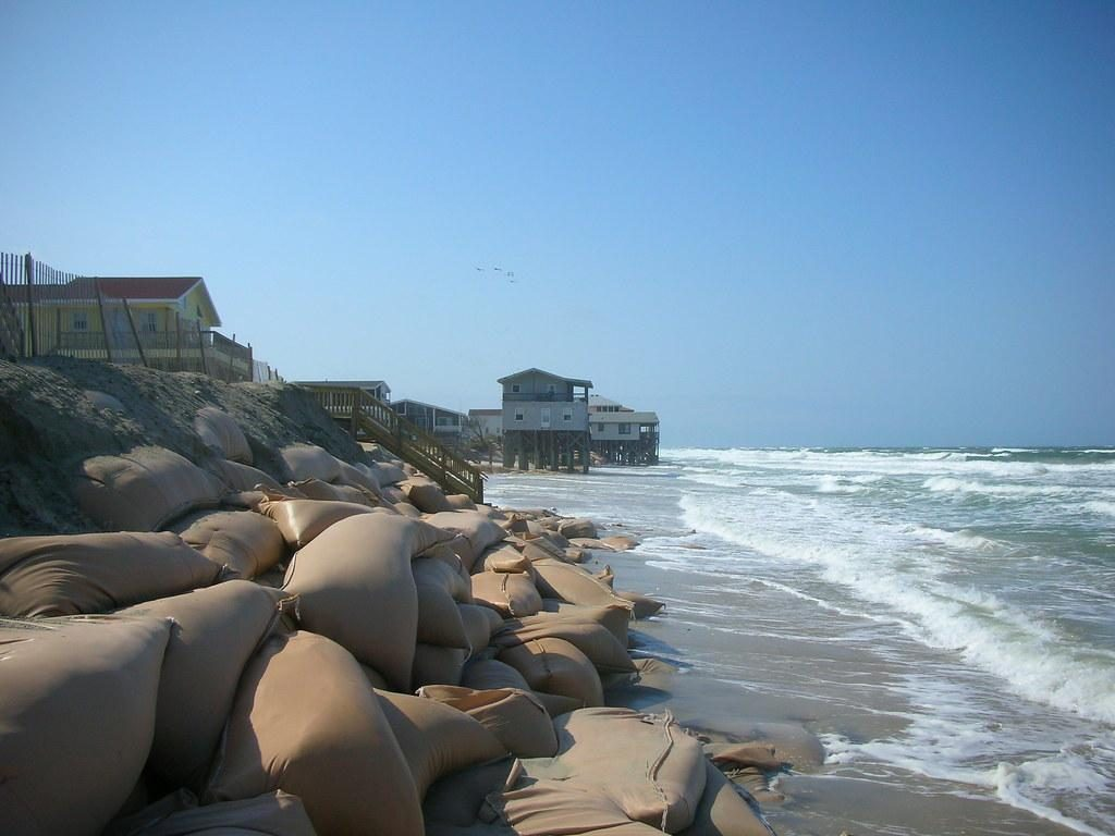 In this landscape photograph, houses along the beach extend to the horizon, each standing on pilings as the sand below the houses due to the sand below the houses eroding away. In the foreground a pile of large brown sandbags are piled along the shoreline in a failed attempt to protect homes from further beach erosion. Whitecapped waves crash along the beach.
