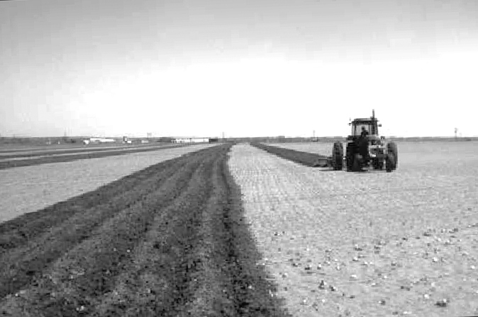 A tractor pulls a plow through a field to add ridges and increase surface roughness of the soil.