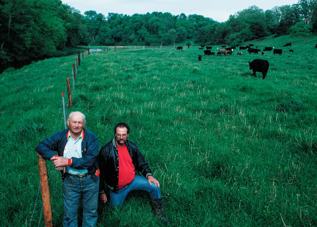 Two men pose next to a barbed wire fence keeping the cattle in the picture out of the nearby stream.