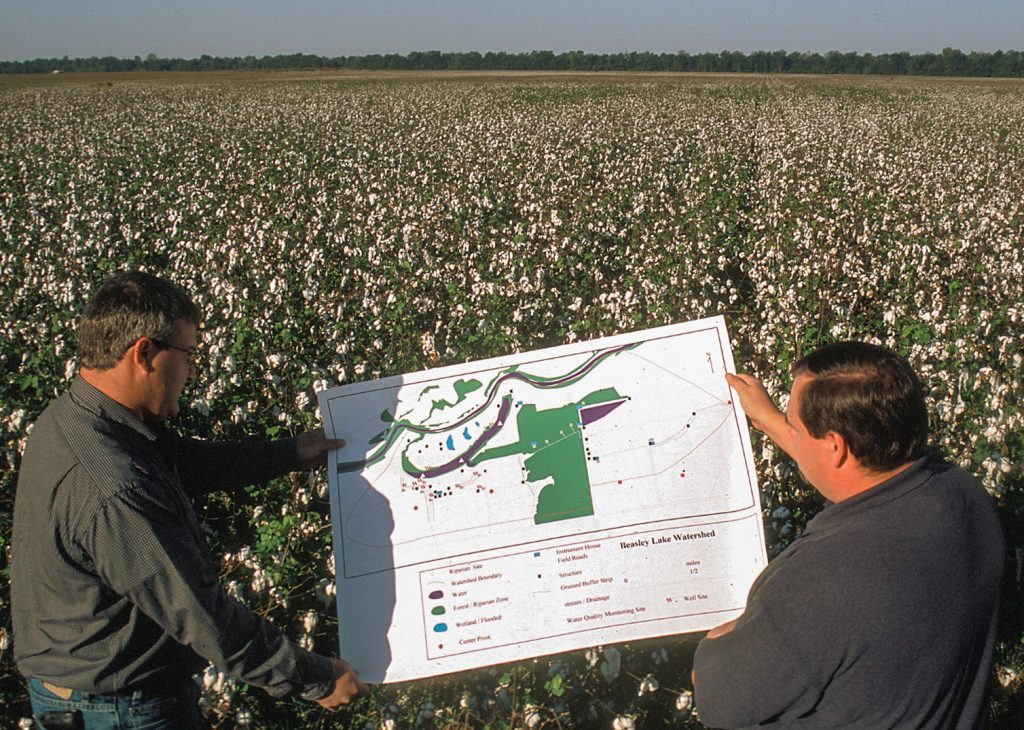 Two men hold up construction plans for a wetland restoration project planned for the cotton field in which they are standing.