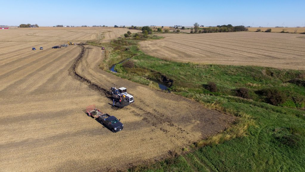 The view from an airplane of a drainage tile machine being used to install a saturated buffer distribution line in a harvested field along a stream in what is to become a saturated buffer.