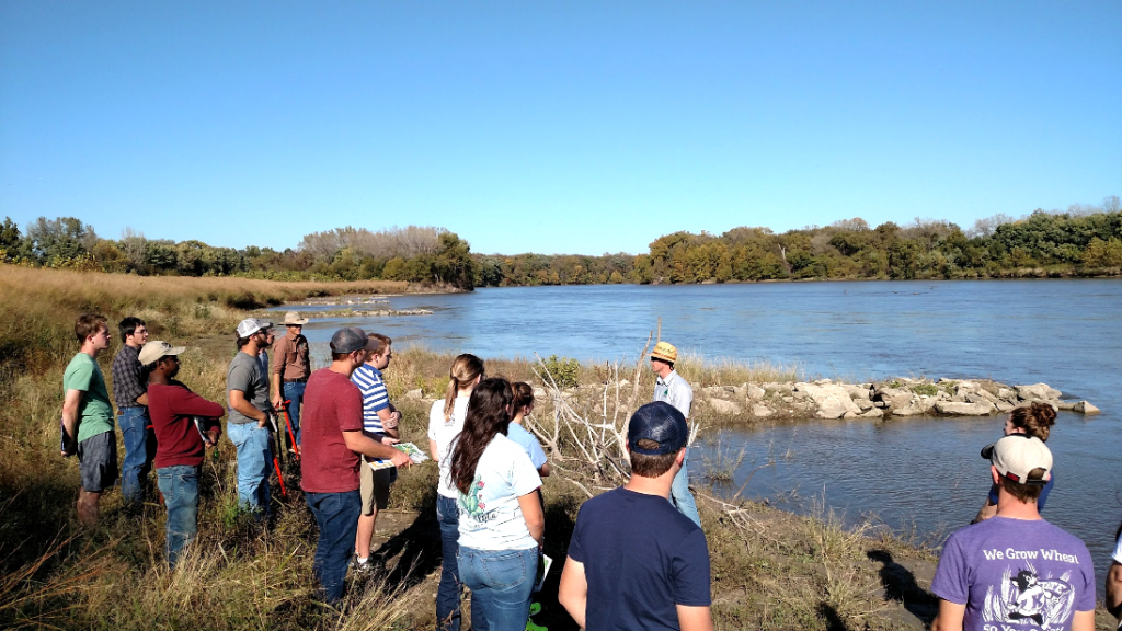 College students tour a riparian buffer strip on the banks of a river