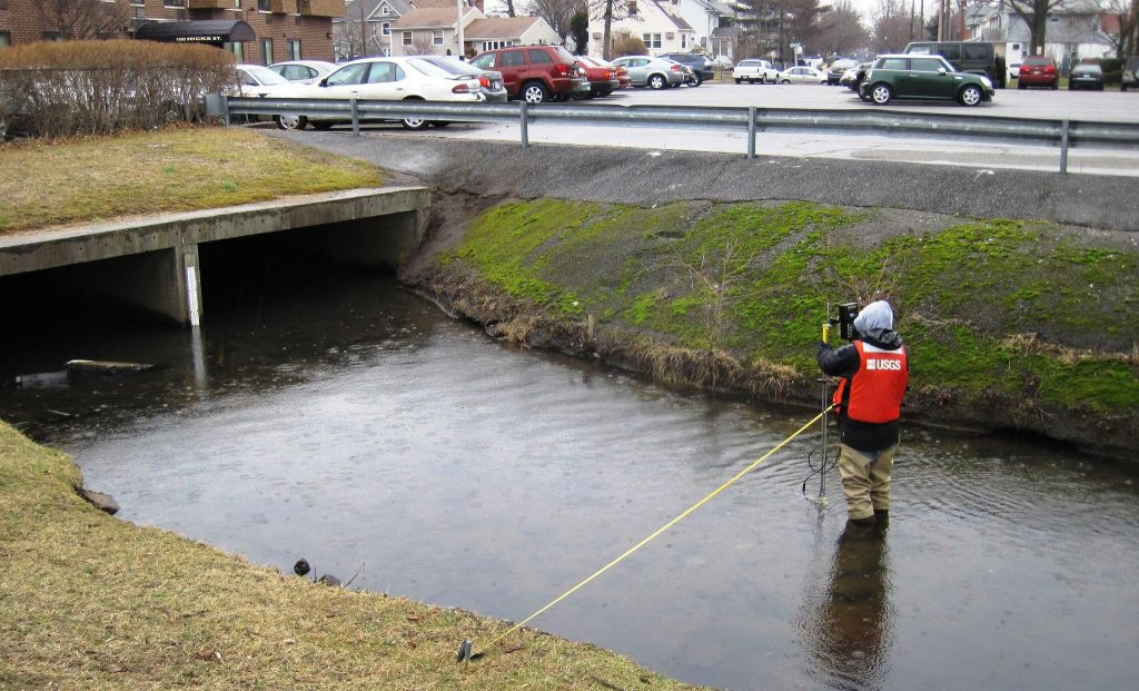 A hydrologist standing in a stream uses an instrument to measure stream discharge.