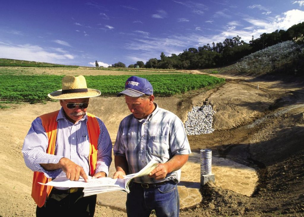 NRCS employees reviewing construction plans with a sediment basin behind them. The sediment basin is a low spot for gathering water, and a pipe extends upward to allow stored runoff water to slowly drain from the basin.
