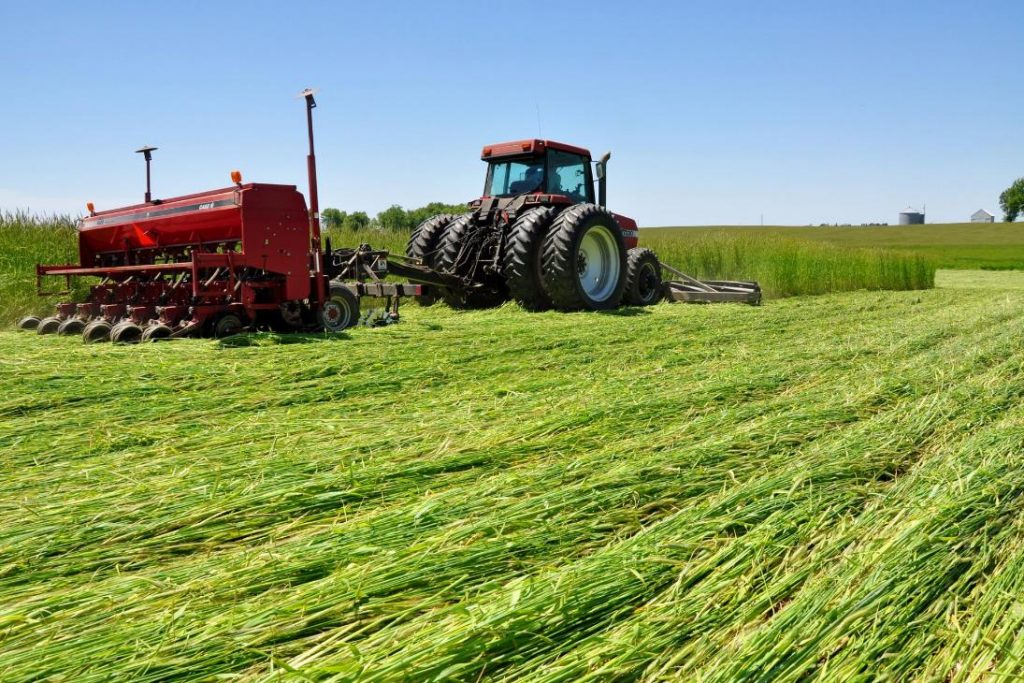 A tractor with a roller crimper implement in front of the tractor knocking down cover crops in a field, and a seed drill behind the tractor planting the next cash crop.