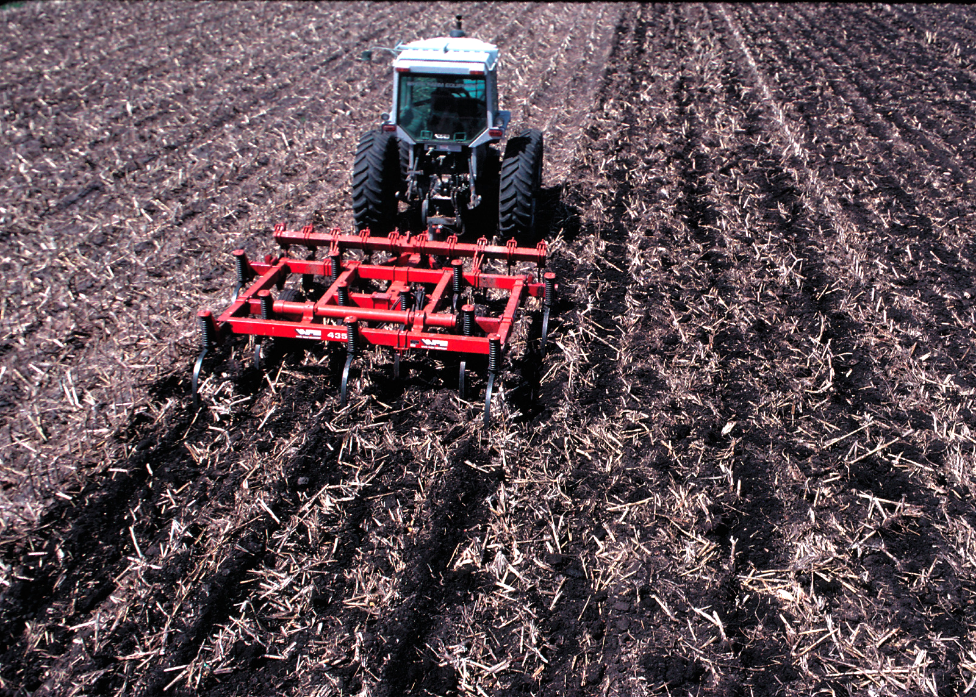A tractor pulling a plow leaving much of the crop residue from the previous crop on the soil surface.