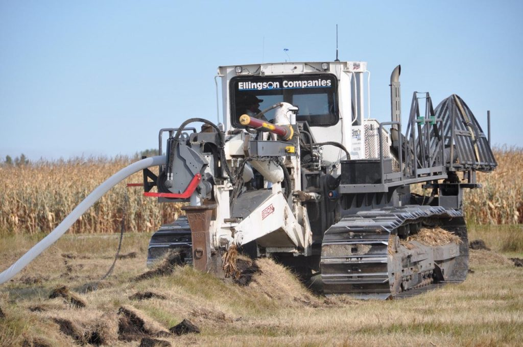 A tiling machine installing tile line in a field.