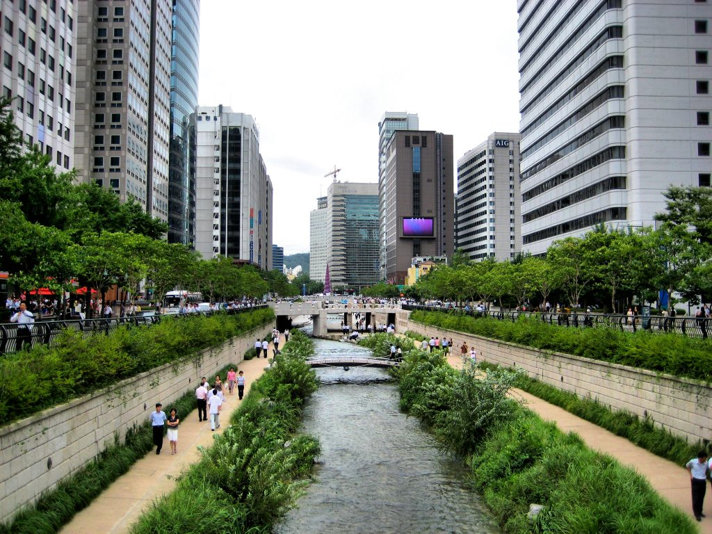An urban stream lined with pedestrian walkways, retaining walls, city streets, and high rise buildings.