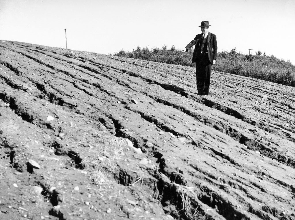 A mand stands on an eroded slope and pointing.