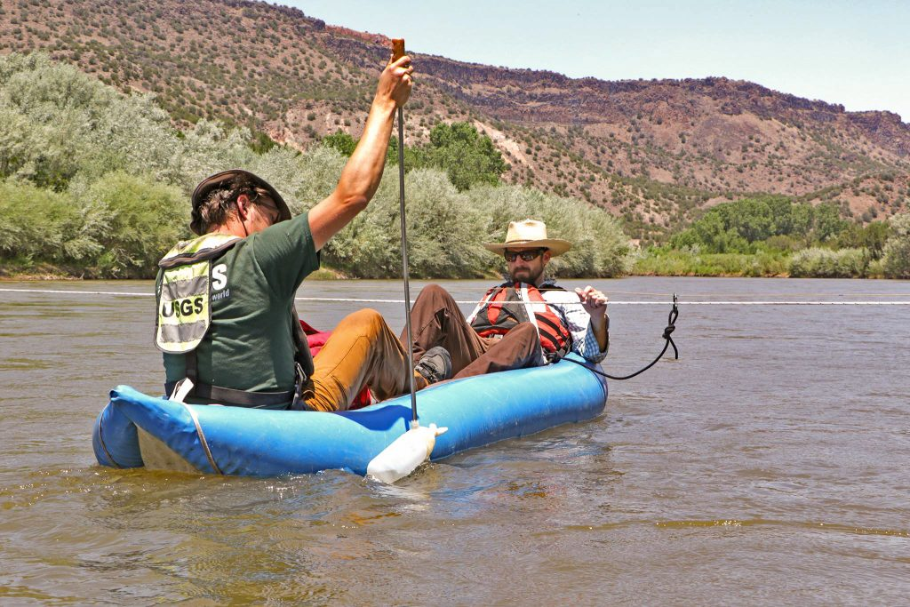 Two scientists collect river water samples from a boat