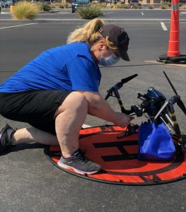 A DroneUp employee prepares a Covid-19 test kit for delivery.